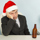 Sad man suffering from hangover after Christmas — Stock Photo