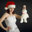 Young womin Christmas cap holds rabbit — Stock Photo #4372545