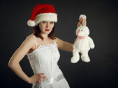 Young woman in Christmas cap holds a rabbit — Stock Photo