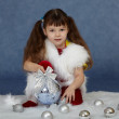 Child sits on blue with Christmas tree ball — Stock Photo
