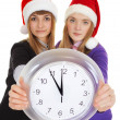 Two girls in New Year's caps with clock — Stock Photo