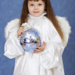 Child dressed as an angel with wings holding glass ball — Stock Photo