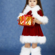 Little girl in fur New Year's clothes with gift — Stock Photo