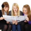 Three young girls reading newspaper - Stock Photo