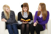 Young girls read fiction on couch — Stock Photo