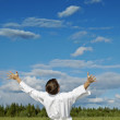 Person has lifted hands to blue sky - happiness - Stock Photo