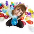 Royalty-Free Stock Photo: Young woman sitting on floor among balloons