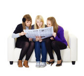 Three girlfriends teen read the newspaper — Stock Photo
