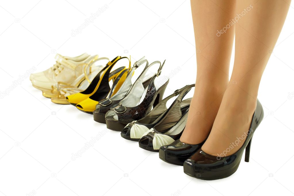 Female legs in high heels and a number of different summer shoes — Stock Photo #4899412