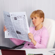 Beautiful young girl reads newspaper — Stock Photo