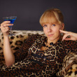 Girl in leopard dress, drinking a blue cocktail — Stock Photo