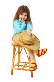 Child sits on an old wooden chair with hat — Stock Photo