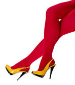 Beautiful female legs in yellow shoes and red tights — Stock Photo