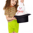 Child gets rabbit out of a hat like magician on white — Stock Photo