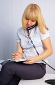 Secretary takes calls while sitting on table — Foto Stock
