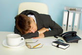 Tired man sleeping on a table — Stock Photo