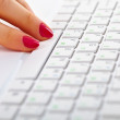 Female fingers on white laptop keyboard — Stock Photo