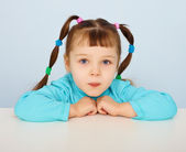 Little girl sitting at desk — Stock Photo