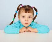 Little girl sitting at desk — Stock fotografie