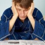 Sad man reading a newspaper — Stock Photo