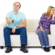 Husband and wife in a quarrel sit on couch watching TV — Stock Photo