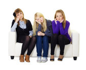 Young girls are sad sitting on couch — Stock Photo