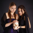 Two young girls with a human skull — Stock Photo