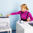 Young woman - secretary prints out a document — Stock Photo