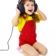 Little girl sitting on white with large earpieces — Stock Photo