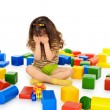 Little girl sitting on white among toys and crying - Stock Photo