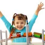 Joyful girl playing with toy railway — Stock Photo #5370141