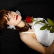 Beautiful girl with rose in hand lying on black — Stock Photo