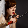 Royalty-Free Stock Photo: Girl lipstick looking at blade of sword