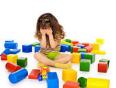 Little girl sitting on white among toys and crying — Stock Photo