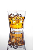 Glass of scotch whiskey and ice on glass table — Stock Photo
