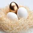 One golden egg and two white egg in the nest — Stock Photo