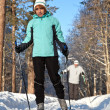 Man and woman walk on ski in winter forest - Stock Photo