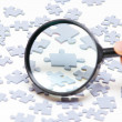 Magnifying glass and puzzle — Stock Photo #5378125