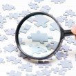 Magnifying glass and puzzle — Stock Photo