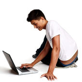 Fundersam ung man sitter på golvet med laptop, isolerad på whi — Stockfoto