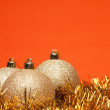 Gold shiny christmas balls with tinsel over orange background — Stock Photo #4524526