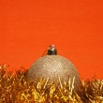 Shiny christmas ball with tinsel over orange background — Stock Photo #4558563