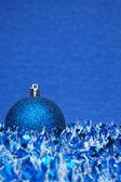 Blue shiny christmas ball with tinsel — Stock Photo