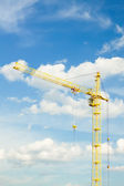 Tower crane against blue cloudy sky — Stock Photo