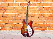 Brick wall and guitar — Stock Photo