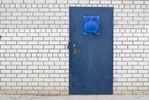 Niebieskie drzwi stalowych w biały cegła — Zdjęcie stockowe