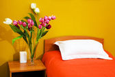 Bed with an orange coverlet — Stock Photo