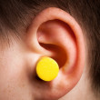 Yellow earplug - Stock Photo