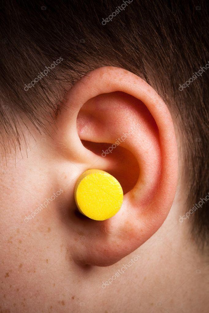 Yellow earplug into the ear close up — Stock Photo #5125367