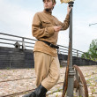 Retro style picture with soldier at tram stop. — Stock Photo